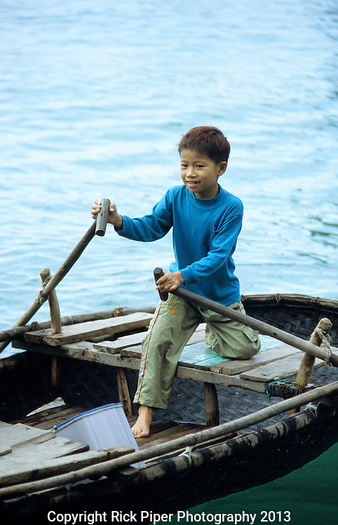 Vietnamese Boy - Young Vietnamese boy in small rowing boat, Halong Bay, Viet Nam