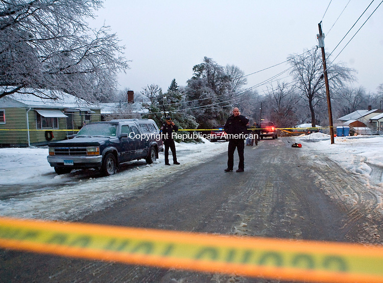 WATERBURY, CT - 07 JANUARY 2009 -010709JT03-<br /> Waterbury police officers and other emergency workers investigate the scene where a woman was struck by a large tree branch as she was walking in front of 306 Mansfield Avenue on Wednesday in Waterbury. The woman sustained serious head injuries. Buckling under the weight of ice that accumulated during Wednesday's ice storm, the tree also brought a telephone pole down with it, resulting in downed power and telephone lines at the intersection of Highlawn Street.<br /> Josalee Thrift / Republican-American
