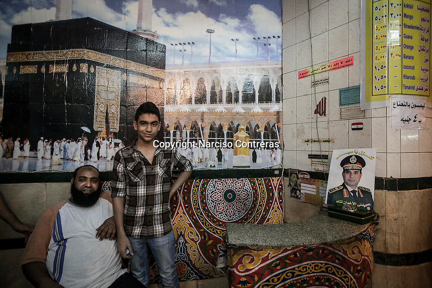 In this Saturday, Jul. 13, 2013 photo, two man pose for photo beside a poster of the General Abdel Fattah al Sisi inside a juice parlor in the nearby streets of Tahrir Square in Cairo, Egypt. (Photo/Narciso Contreras).