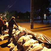 DOBRZYKOW, POLAND, MAY 24, 2010:.Villagers standing by the sand bags wall, early morning, observing rising waters..The latest chapter of disastrous floods in Poland has been opened yesterday, May 23, 2010, after Vistula river broke its banks and flooded over 25 villages causing evacualtion of most inhabitants..Photo by Piotr Malecki / Napo Images..DOBRZYKOW, POLSKA, 24/05/2010:.MIeszkancy przy scianie z workow z piaskiem obserwuja podnoszaca sie wode wczesnym rankiem . Najnowszy akt straszliwych tegorocznych powodzi zostal rozpoczety wczoraj gdy Wisla przerwala waly na wysokosci wsi Swiniary kolo Plocka..Fot: Piotr Malecki / Napo Images ..