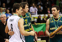 Boomers captain Adam Gibson reluctantly hands over the Al Ramsay Shield to Tall Blacks captain Kirk Penney (left) as Joseph Ingles (centre) looks on during the International basketball match between the NZ Tall Blacks and Australian Boomers at TSB Bank Arena, Wellington, New Zealand on 25 August 2009. Photo: Dave Lintott / lintottphoto.co.nz