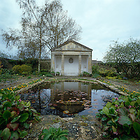 A neo-classical garden room in the walled garden of an English country house is reflected in the dark waters of the lily pond