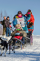 Misha Wiljes and team run past spectators and down the Cordova Street hill with an Iditarider in the basket and a handler during the Anchorage, Alaska ceremonial start on Saturday March 4th during the 2017 Iditarod race. Photo ©2017 by Daniel Lent/SchultzPhoto.com