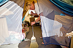 RENO, NV - OCTOBER 6:  Mary Jackson sweeps out her tent in a tent city for the homeless in downtown Reno, Nevada October 6, 2008. Jackson works odd jobs and her husband, a veteran, works 18 hours per week, but they're unable to make enough money to afford housing. The City of Reno set up the tent city when existing shelters became overcrowded as Nevada struggles with one of the highest unemployment rates in the country. (Photo by Max Whittaker/Getty Images)
