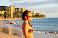 A woman gazes out at the sunset from Ka'anapali Beach, Maui.