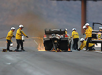 Oct 29, 2016; Las Vegas, NV, USA; NHRA safety safari rescue crews on the scene to extinguish flames after funny car driver Jon Capps crashed into the wall after losing his steering during qualifying for the Toyota Nationals at The Strip at Las Vegas Motor Speedway. Capps was uninjured in the incident. Mandatory Credit: Mark J. Rebilas-USA TODAY Sports