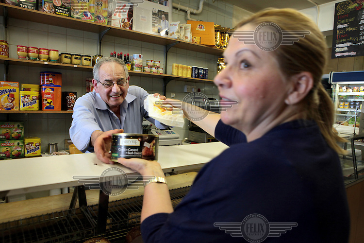 Louis, the French owner of The Deli in Bute Street, South Kensington, London, serves a customer with typical French produce.