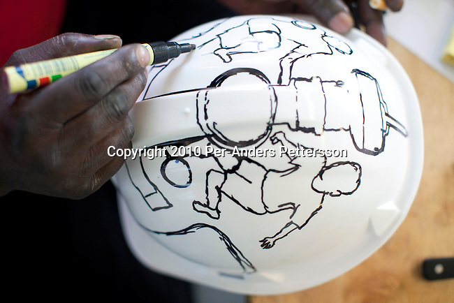 JOHANNESBURG, SOUTH AFRICA - MAY 10: Alfred Baloyi, an artist, designs a Makarapa Helmet in his new studio in Wynberg, north of Johannesburg, South Africa. Mr. Baloyi, and a diehard Kaizer Chiefs soccer fan, started to make these hats in 1979. Initially he asked a friend who worked at a construction site for a helmet, as he wanted to protect himself from missiles at games. He later started to paint it, and later started to make this different figures hand cut out from the helmet. During the years he has made many different artistic hats that are on display in his studio in a shack in Primrose, Johannesburg. He later gave up his job as a washer of busses. From his small workshop in a squatter camp in Primrose south east of Johannesburg he recently made partner with an investor and have a brand new factory with about fifty people employed to make the hats. (Photo by Per-Anders Pettersson/Getty Images)