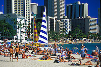 Waikiki beach with tourists lining the beach and catamarans
