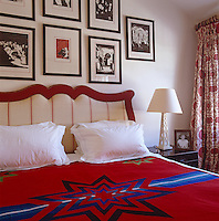 Detail of the studded fabric headboard in this red and white bedroom with framed engravings on the wall