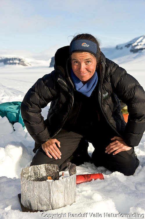 Dame fyrer primus. Wahlenbergbreen, Svalbard. ----- Woman priming stove. Wahlenbergbreen, Svalbard.