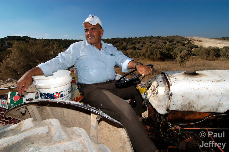 Near Jayyous, Shareef Omar Khaled sits on his tractor near the wall Israel is building inside the West Bank. Khaled is losing much of his farmland to the wall, and promises to nonviolently resist.