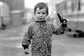 A young boy plays with a toy gun on a local authority Traveller site in Southwark, South London.