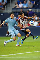 Chivas USA's Francisco Mendoza (stripes) gets past Sporting KC defender Matt Besler... Sporting KC and Chivas USA played to a 1-1 tie at LIVESTRONG Sporting Park, Kansas City, Kansas.