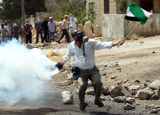 A Palestinian Protestor throws back a tear gas canister towards Israeli troops during clashes following a weekly protest against the Jewish settlement of Kdumim, near Nablus,in the northern West Bank village of Kufr Qaddum, June 29, 2012. Photo by Nedal Eshtayah