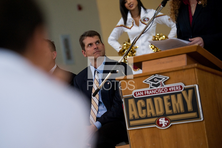 EAST PALO ALTO, CA - JUNE 6: Former football head coach Jim Harbaugh listens to speakers as Stanford announces a Summer partnership with the San Francisco 49ers Academy benefitting underprivileged youth in East Palo Alto.