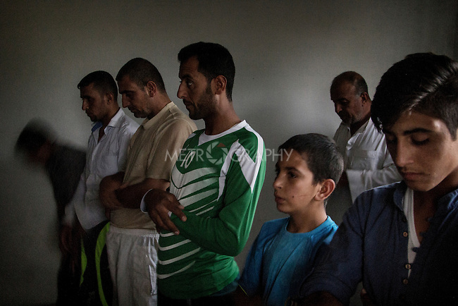 04/07/2015 -- Dibaga-Makhmur-, Iraq -- A group of displaced men from Jarallah village pray before Iftar during the holy month of Ramadan inside a room which was turned into a mosque, at the chicken farm in Dibaga. All the villagers are Sunni Arab. They are very religious and pray five times a day accordingly to the Quran.