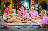 VIETNAM, Ho Chi Minh, Saigon, four girls playing barefoot in front of a home entrance, wearing pink clothes