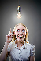 Young blonde woman underneath lit light bulb, finger pointing up