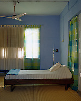 Sheer silk and cotton scarves, inspired by saris, are used as curtains in this guest bedroom