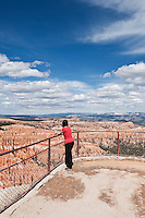 Female tourist enjoys view from Inspiration point, Bryce Canyon national park, Utah, USA