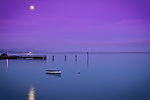 Washington, Bellingham. A small boat rocks softly on Bellingham Bay under morning moonlight.