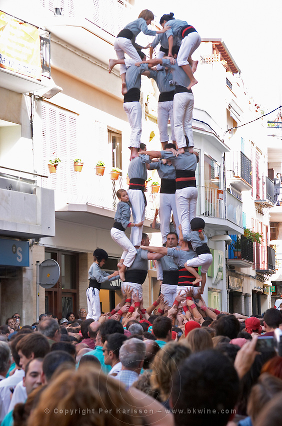 Human tower competition, castellers,  Climbing up. Drawing big crowds. Sitges, Catalonia, Spain