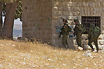 IDF soldiers take cover as they prepare to chase Palestinian youths that had been stoning them into the village of An Nabi Salih near Ramallah on 11/06/2010. The stoning began about twenty minutes after the peaceful end to a demonstration by the Palestinian residents of An Nabi Salih against the planned demolition of village houses by the Israeli military. The soldiers responded with CS gas & rubber bullets before chasing the youths back into the village & arresting three Israeli Peace activists.