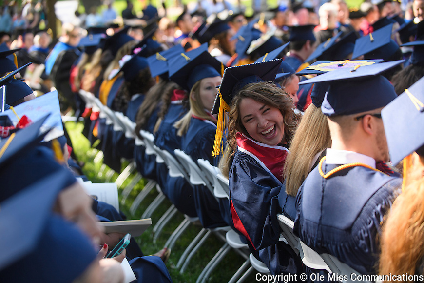 A graduate shares a laugh with a friend during the University of Mississippi's 2016 Commencement Saturday. Photo by Thomas Graning/Ole Miss Communications