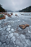 A winter storm brews over the Bubbles and a snow- and ice-covered Jordan Pond in Acadia National Park, Maine