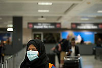 A Dulles International Airport worker assists passengers as they arrive from Dubai after a 14-hour flight on Emirates flight 231, at the international terminal at Dulles International Airport in Dulles, Va., Monday, March16, 2020. Some people are taking the precaution of wearing face masks as they arrive to be greeted by family and or friends. Credit: Rod Lamkey / CNP/AdMedia