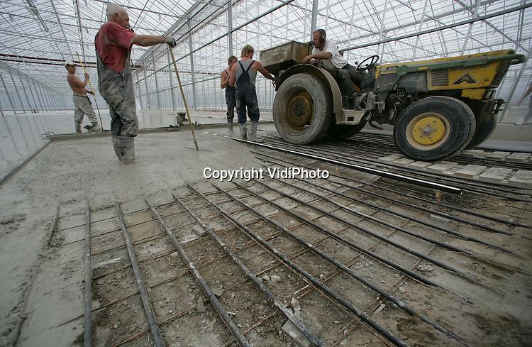 37MT6..Foto: VidiPhoto..BEMMEL - In de nieuwe kassen van Stef Huisman op Bergerden bij Bemmel wordt beton gestort op de leidingen. De leidingen moeten de warmte in de kas transporteren.