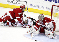 Wisconsin's John Ramage takes down UNO's Brock Montpetit as the puck slides in front of goalie Scott Gudmandson during the second period. Ramage was whistled for tripping on the play. No. 16 UNO beat No. 7 Wisconsin 4-1 in front of a school-record crowd of 15,137 Friday night at Qwest Center Omaha.  (Photo by Michelle Bishop)