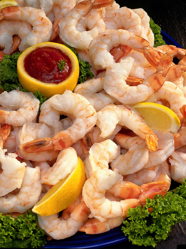 Shrimp with lemons and cocktail sauce.