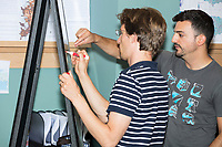 James Saxon, 30, of Chicago, Ill., (with marker) explains a computation method to Daniel McGlone, 32, of Philadelphia, Penn., at the Metric Geometry and Gerrymandering Group (MGGG) hackathon at the Data Lab in the Tisch Library at Tufts University in Medford, Massachusetts, USA, on Thurs., Aug. 10, 2017. Saxon is a post-doctoral associate at the University of Chicago, where he works on gerrymandering. McGlone, 32, is a GIS Analyst at Azavea in Philadelphia, Pennsylvania. The hackathon is part of the first in a series of Geometry of Redistricting workshops put on by the MGGG. Academics, Geographic Information Systems (GIS) professionals, and legal professionals worked together to build tools useful in analyzing voting district data around the country.