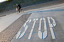 A tilted view of a 'STOP' road marking at an intersection, a commuter riding a bicycle in the background.  Mountain View, California, USA