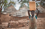 A girl carries water in Lugi, a village in the Nuba Mountains of Sudan. The area is controlled by the Sudan People's Liberation Movement-North, and frequently attacked by the military of Sudan. The church has sponsored wells, schools and health care facilities throughout the war-torn region.