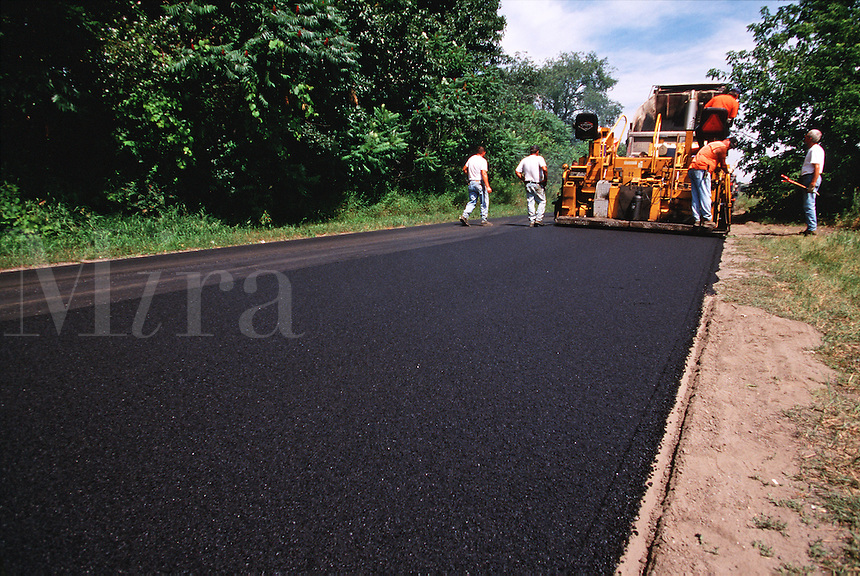 Work crew paving road.