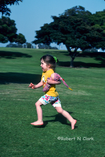 Girls running in park carrying her doll under her arm, smiling with one foot lifted off the ground