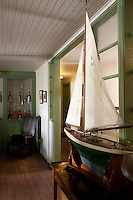 In the tasting rooms of the Lagavulin distillery an antique model of a sailing boat is displayed on an antique table whilst bottles of whisky can be seen in a glass-fronted cabinet behind