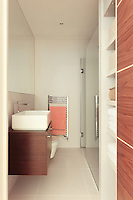 White folded towels are stored neatly in built-in shelving in a modern bathroom. A shower cubicle has a glass door and a washbasin sits on a wooden unit.
