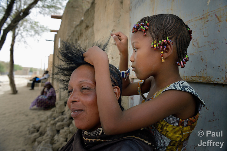 Back home in Timbuktu, Mali, after a year of living in the nation's capital, Bamako, Aissata Kantao gets her hair worked on by her 8-year old daughter Mariam. Kantao and her five children fled Timbuktu after the north of Mali was seized by Islamist fighters in 2012. She returned in 2013 several months after it was liberated by French and Malian soldiers, but hasn't found work in the war-torn city.