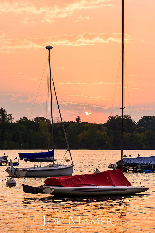 Sailboats moored on Lake Harriet at dawn.