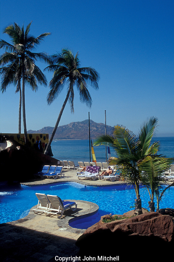 Tourists relaxing beside a hotel swimming pool in the Zona Dorada or Golden Zone, Mazatlan, Sonaloa, Mexico
