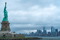 The NYC skyline is shrouded in clouds on a rainy day.