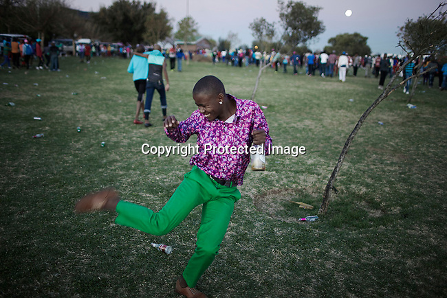 SOWETO, SOUTH AFRICA SEPTEMBER 29: An Izikhothane youth dances and shows off his clothes and shoes on September 29, 2012 in Thokoza Park, Soweto, South Africa. Hundreds of Izikhothane kids gathered in Thokoza Park and moved on to other areas in Soweto, to show off their dance moves and play loud music. The Izikhothane bling kids are the new fears of residents and parents in the townships of Johannesburg. They buy (and sometimes burn and destroy) fancy brand clothes and shoes in Soweto. They also like to drink and display expensive bottles of alcohol. Many of these kids are desperate to get the latest clothes and the pressure is hard on their parents. (Photo by: Per-Anders Pettersson)