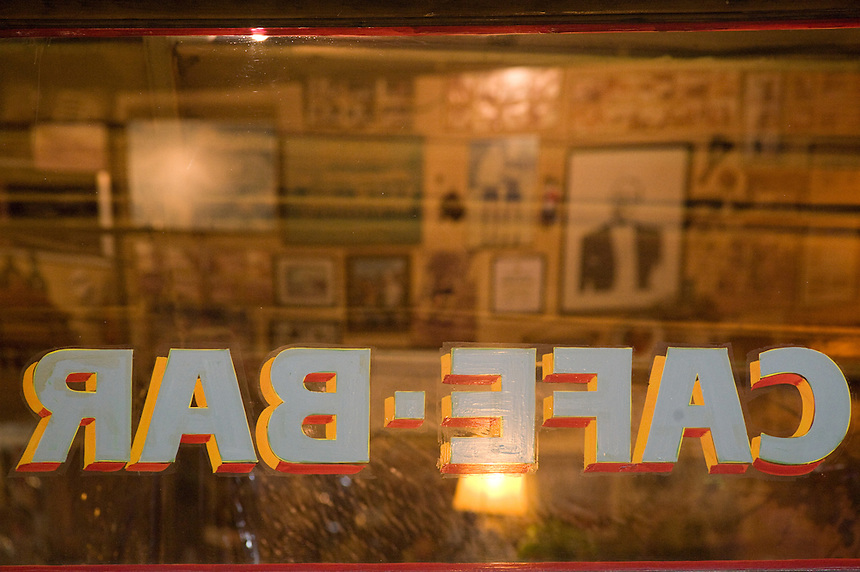"Sports memorabilia and homages to tango singer Carlos Gardel reflect in the windows at Cafe de Garcia in Buenos Aires'  Villa Devoto neighborhood. Garcia, opened in 1937 by the Garcia family, wears its past on its ""sleeves."" A Boca Junior T-shirt signed by Diego Maradona joins accordions, cue sticks, wine skins, rifles, and numerous vintage items on shelves and yellowed walls. (Kevin Moloney for the New York Times)"