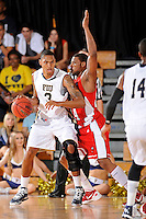 28 January 2012:  FIU guard-forward Dominique Ferguson (3) handles the ball while being defended by WKU guard-forward George Fant (44) in the first half as the Western Kentucky University Hilltoppers defeated the FIU Golden Panthers, 61-51, at the U.S. Century Bank Arena in Miami, Florida.