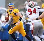 BROOKINGS, SD - NOVEMBER 22:  Austin Sumner #6 from South Dakota State University rolls out looks for a receiver past Drew Iddings #94 from the University of South Dakota in the first half of their game Saturday at Coughlin Alumni Stadium in Brookings. (Photo by Dave Eggen/Inertia)