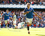 Nikica Jelavic celebrates his goal for Rangers as Scott Brown lies stunned on the ground behind him